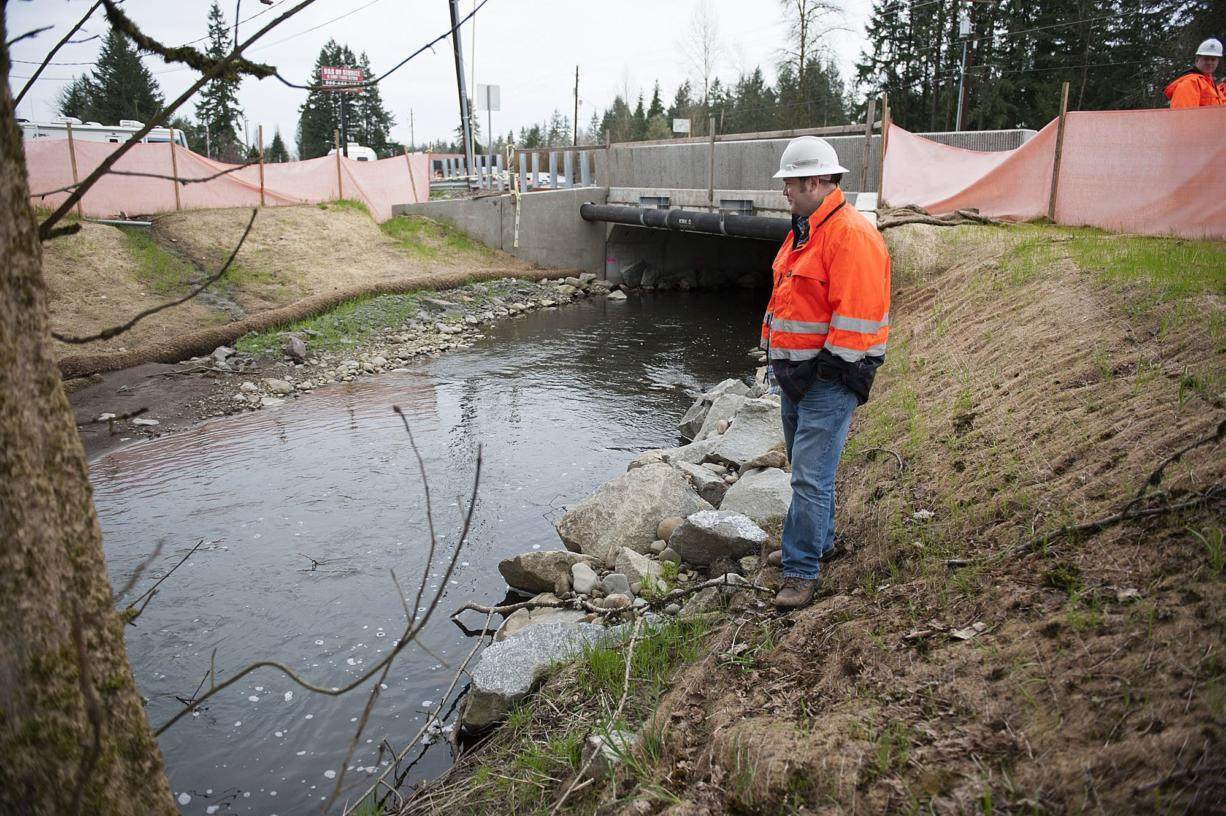 Kevin Workman of the Washington State Department of Transportation looks over a recently constructed culvert at Mill Creek along state Highway 502 near Battle Ground on Monday. Modern culverts are designed and installed to mesh with all life phases of migratory fish. (Amanda Cowan/The Columbian)