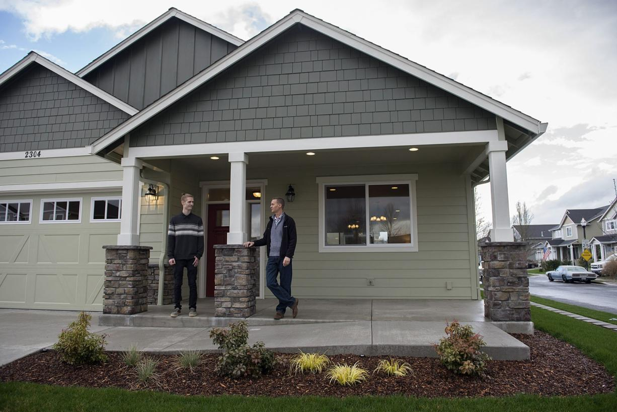 Andrew Olin, 22, of Olin Homes, left, talks with his father, Ivan Olin, 46, as they stand near the front of a model home in Battle Ground that is wheelchair-accessible and designed for aging in place.