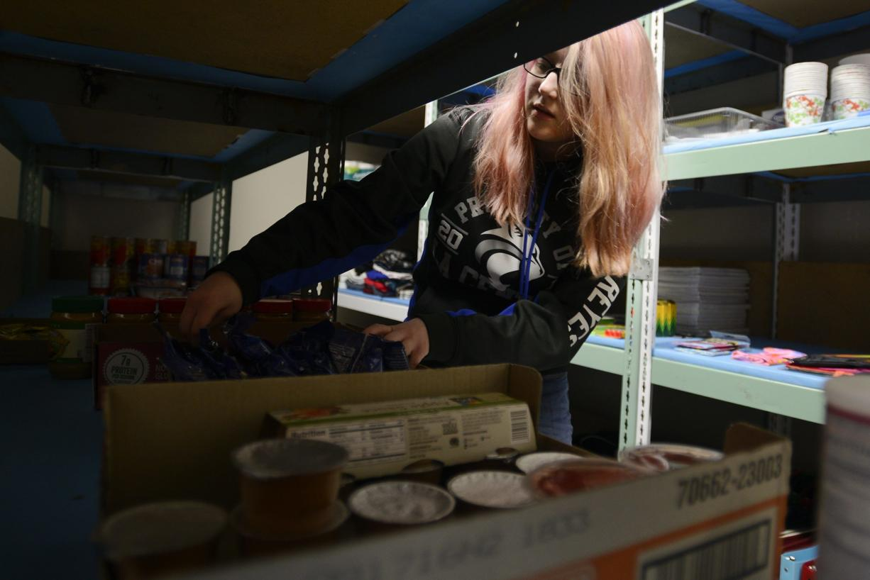 Sophia Reyes, a senior at La Center High School, organizes food in the school's food pantry on Feb. 16. With a growing population of students who are going hungry, the local nonprofit, Lewis River Mobile Food Bank, worked with the school to start the food pantry.