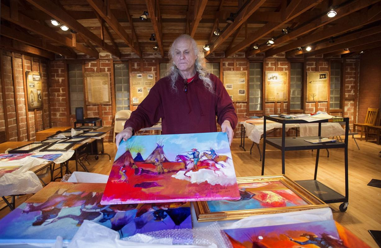 """Roben White holds the painting """"Cowards"""" by Brent Learned while unpacking an exhibit documenting the 1864 Sand Creek, Colo., massacre for the """"One November Morning"""" exhibit at the Clark County Historical Museum. White, a museum volunteer, is a descendant of massacre survivors."""