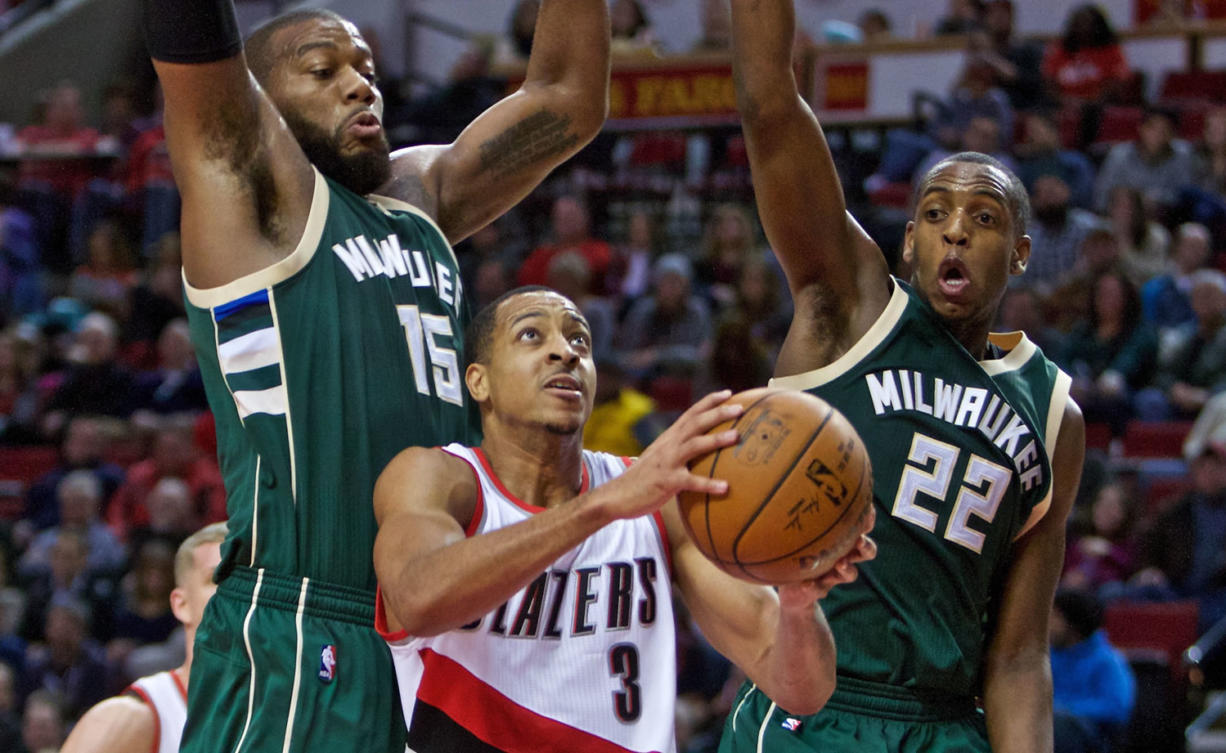 Portland Trail Blazers guard C.J. McCollum, center, shoots between Milwaukee Bucks center Greg Monroe, left, and guard Khris Middleton during the second half of an NBA basketball game in Portland, Ore., Tuesday, Feb. 2, 2016. The Trail Blazers won 107-95.