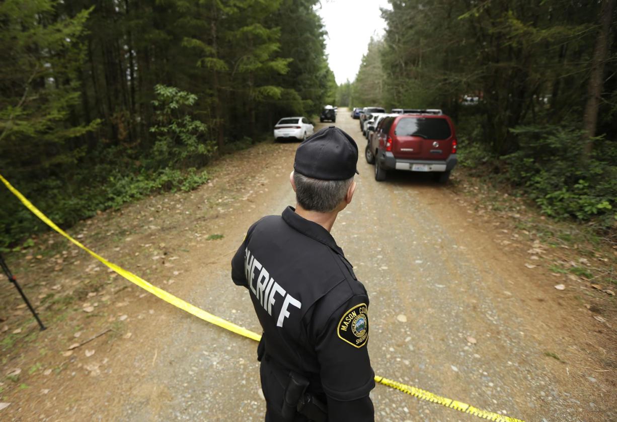 Mason County Sheriff's Chief Criminal Deputy Russ Osterhout looks down a road near the scene of a fatal shooting Friday near Belfair. (AP Photo/Ted S. Warren)