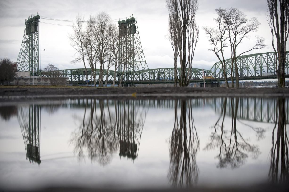 The waterfront and the Interstate 5 Bridge is seen reflected in a puddle left by December rain in Vancouver.