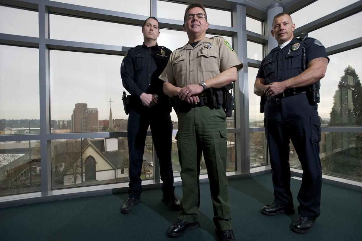 Portland Police Sgt. Peter Simpson, from left, Clark County Sheriff's Deputy Tim Hockett and Vancouver police Officer Taylor Smarr pose for a portrait inside the Clark County Public Service Center in February 2013. The Vancouver Police Department, Clark County Sheriff's Office and Portland Police Bureau had just announced plans to use one central records management system that would allow officers to easily access information from other agencies. The sheriff's office is now saying the system isn't worth the hassle.