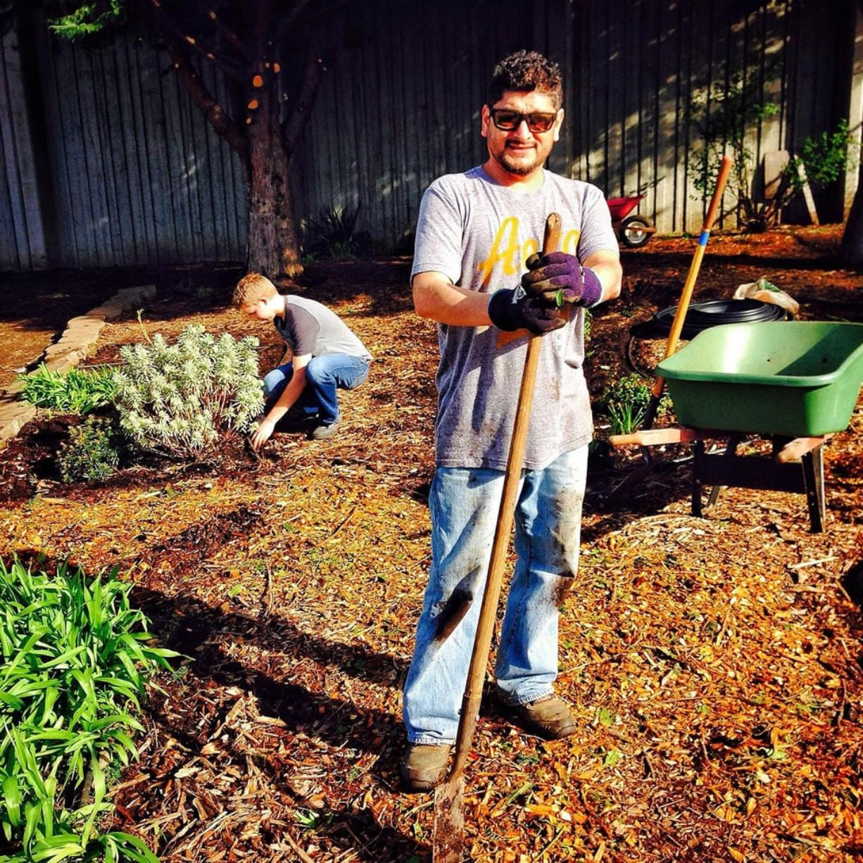 David Malagon-Lopez spreads bark chips while Adam Lindberg weeds in the Butterfly/Hummingbird Garden.