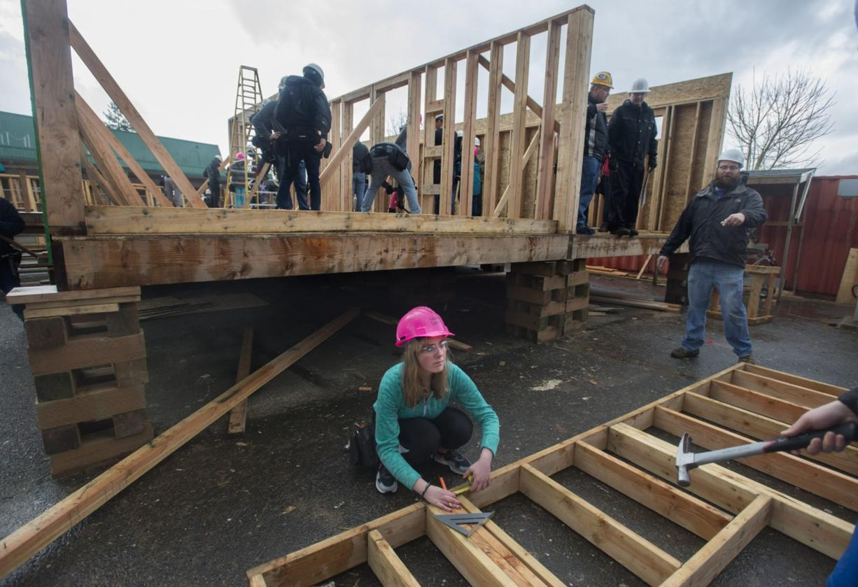 Evergreen High School sophomore Hailey Crater, 15, center, uses her math skills to measure a framed-out exterior wall on a Habitat for Humanity home students are building in their Geometry in Construction class. (Photos by Amanda Cowan/The Columbian)