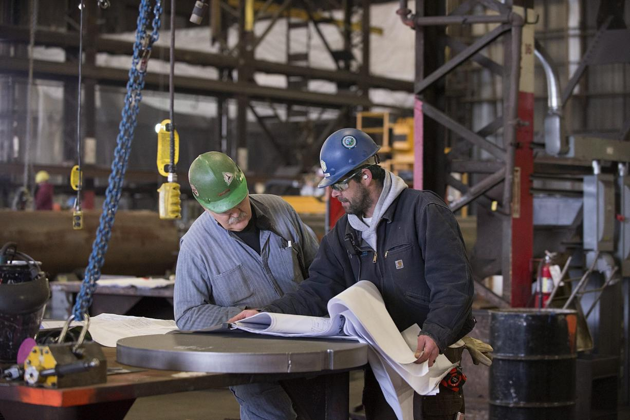 Thompson Metal Fab employees George Mason, left, and Mike Marsh look over shop drawings recently at the company's Vancouver shop. Manufacturing is the only employment sector not growing in Clark County, though officials say there's reason to be optimistic.
