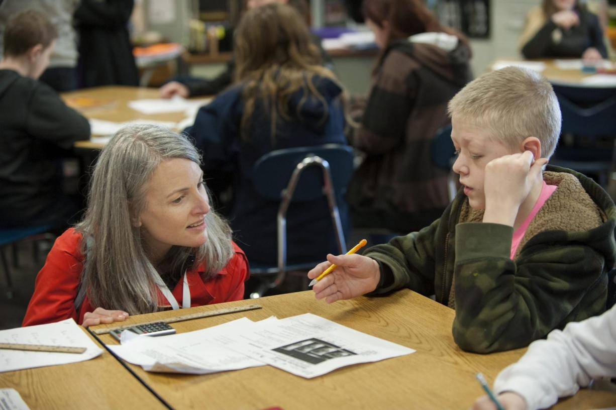 Caroline King, left, chief policy officer for Washington STEM, chats with sixth-grader Hayden Kahler, 11, about calculating the ratios of caffeine to sugar in coffee drinks during his math class Wednesday at Frontier Middle School. (Photos by Amanda Cowan/The Columbian)