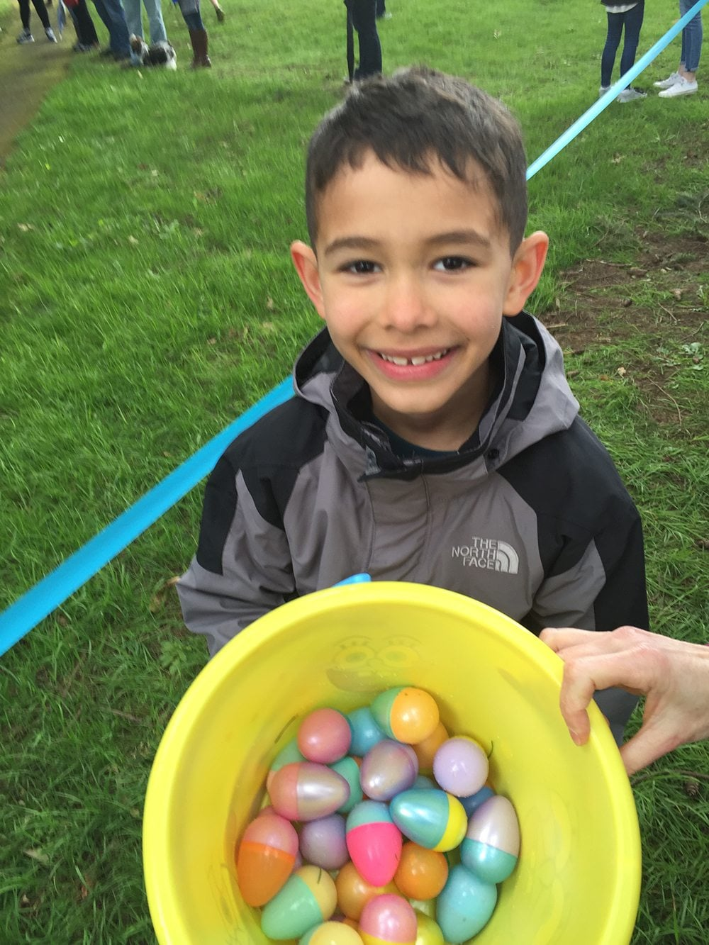 """Brody Olson, 8, of West Linn, Ore., shows off the roughly two dozen plastic Easter eggs he collected Sunday afternoon at an Easter egg hunt at Crown Park in Camas. As for his strategy in this year's hunt: """"I just went random,"""" he said. (Cindi Olson)"""