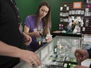 Assistant manager Alex McIntosh helps a customer while working behind the counter at Sticky's Pot Shop in Vancouver last week.