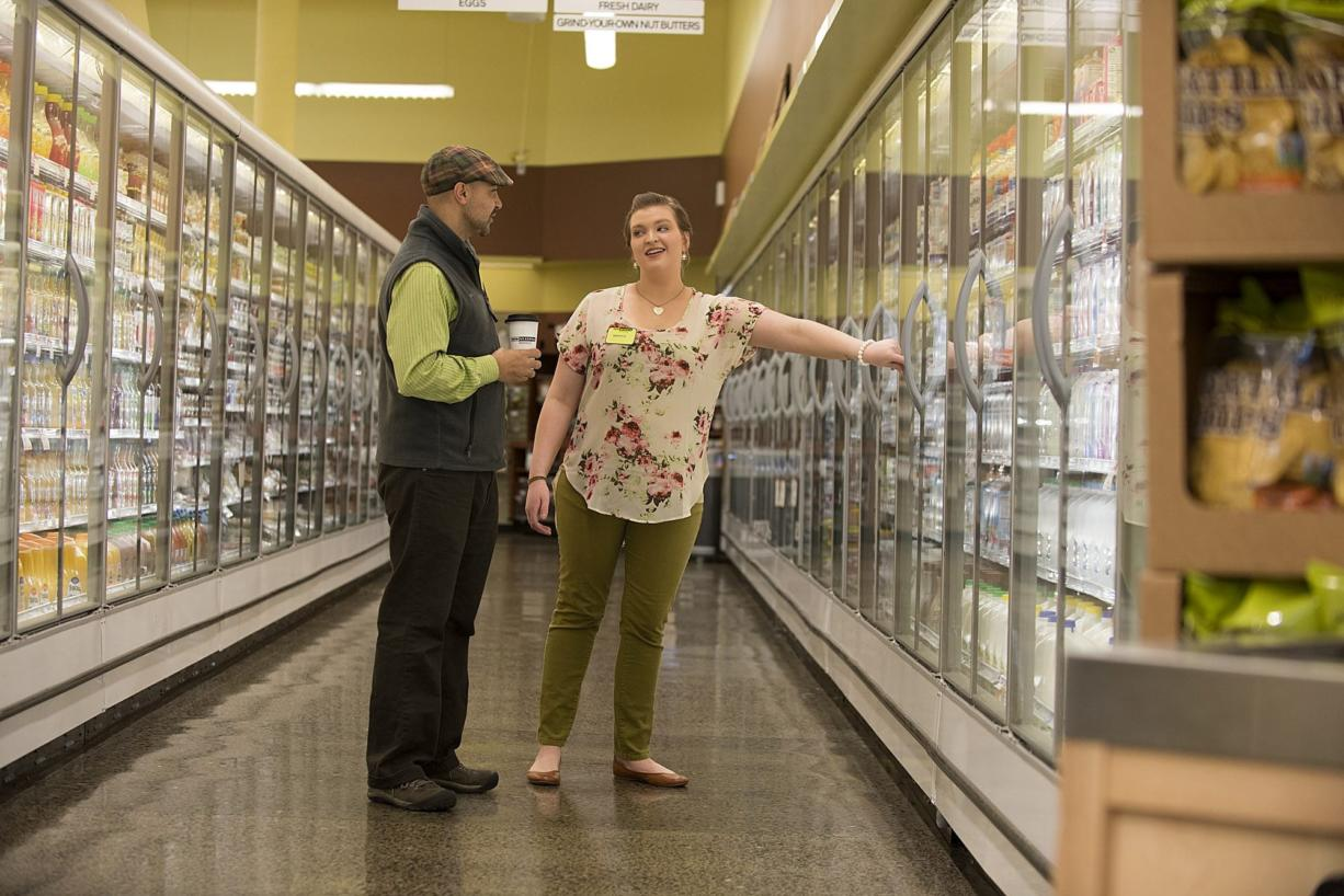 Vancouver New Seasons Market manager Glen Jones, left, and the store's Green Team captain Makayla Karlsen look over energy-saving doors at the store, which was recognized Thursday evening by the Clark County Green Business Program as the Green Business of the Year.