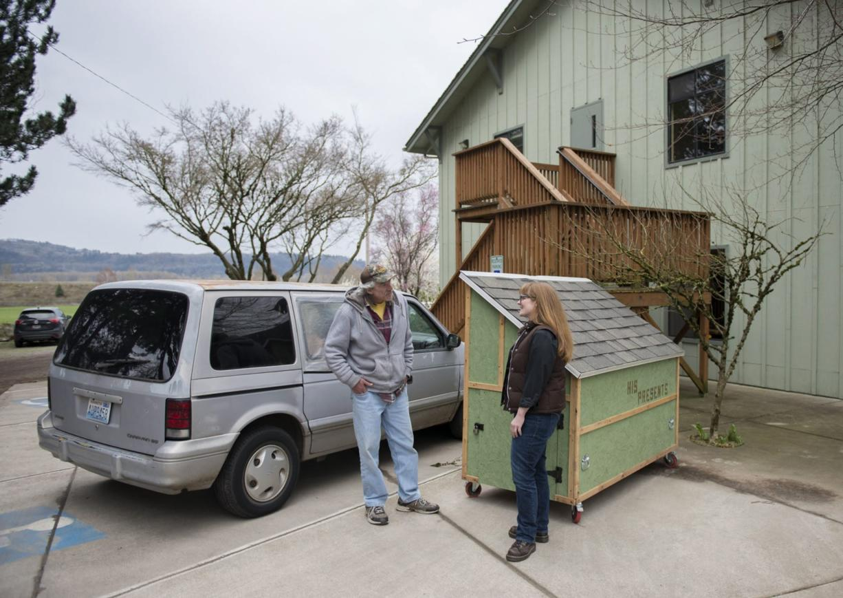 Cory Soderberg, left, talks with the Rev. Jessie Smith near his van and a hut for the homeless in the parking lot at St. Anne's Episcopal Church.