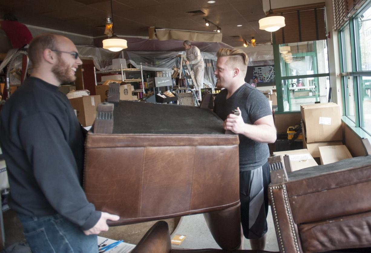 Steven Morgan, right, moves furniture with Wyatt McGehee as remodeling takes place at the Starbucks near Esther Short Park in Vancouver on Monday.
