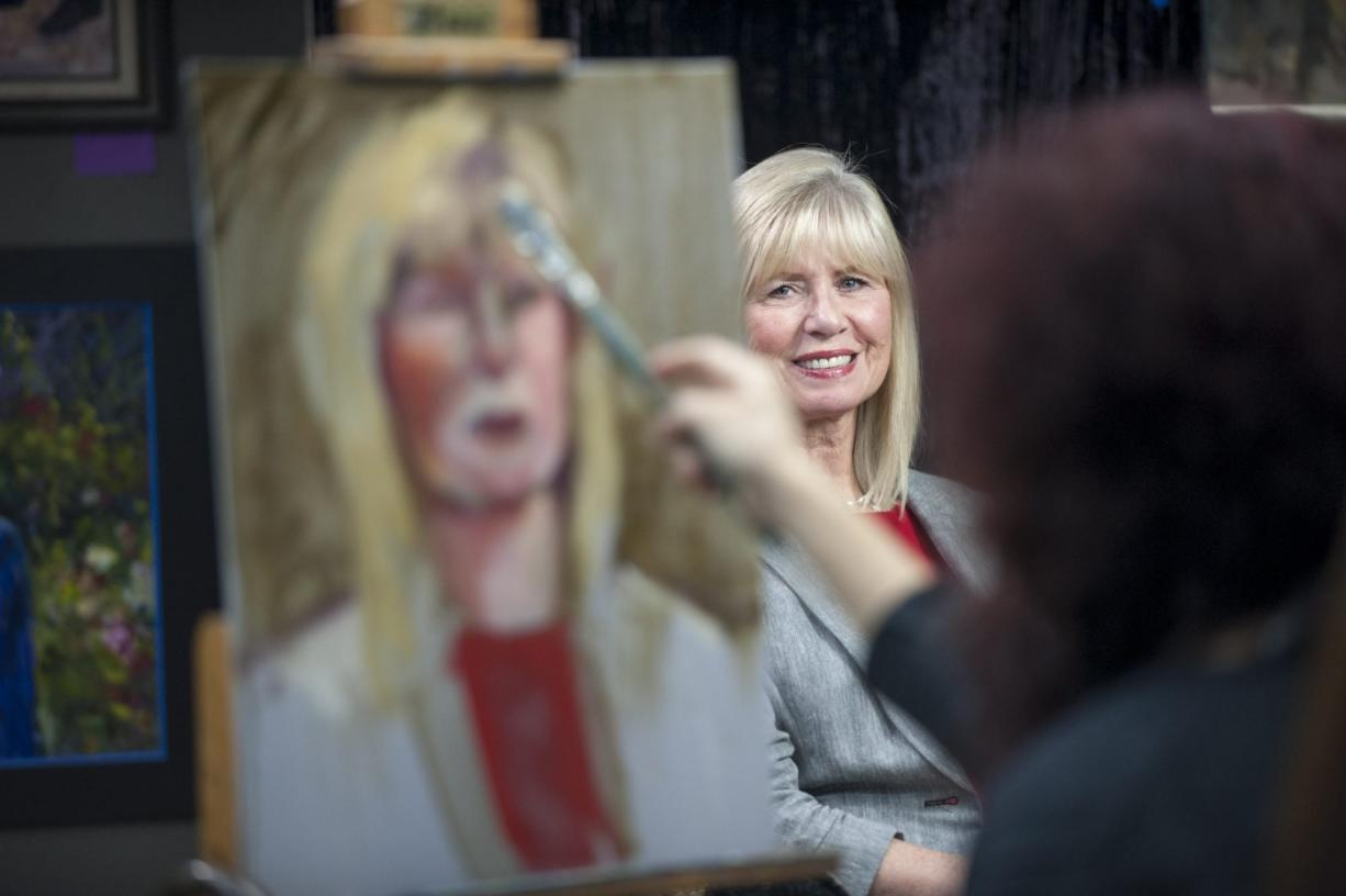 Local artist Hilarie Couture works on Linda Glover's portrait as part of an art project recognizing 40 notable Clark County women, past and present.