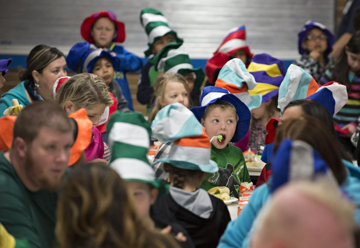 First-grader Jordan Terry, wearing green shirt and holding fork, is surrounded by a sea of Dr. Seuss hats as he eats his green eggs and ham Tuesday morning at Ellsworth Elementary School.