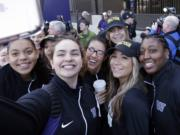 Washington players huddle together for a selfie during a sendoff rally for the Washington women's basketball team. The Huskies play Syracuse in a national semifinal on Sunday. Prairie graduate Heather Corral is seen in the center, wearing glasses.