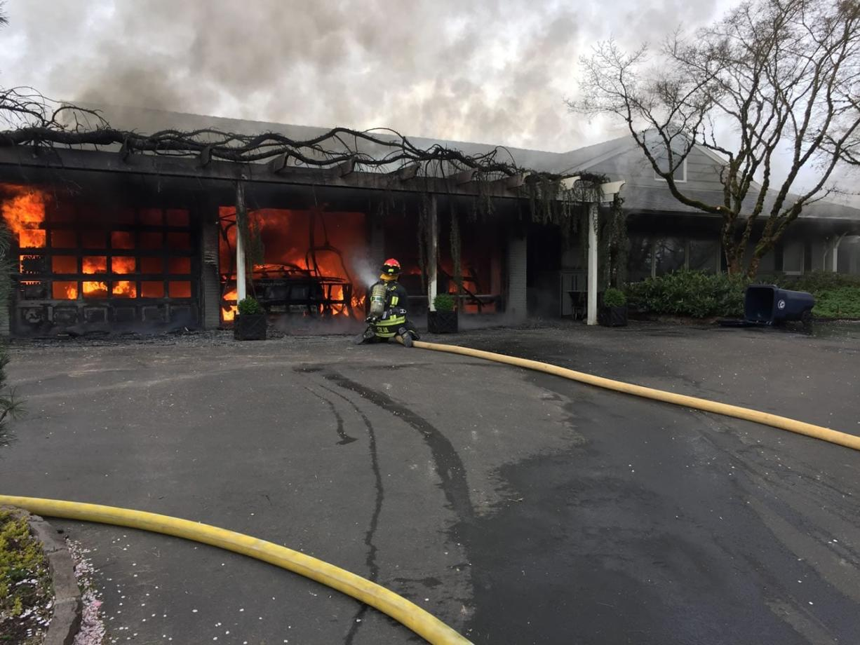 Firefighters are working to extinguish a garage fire at a Camas residence.