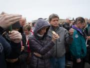 Crowd members light candles in memory of John McKibbin at Pearson Field on Saturday, March 26.