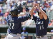 Seattle Mariners' Robinson Cano (22) is congratulated by Kyle Seager (15) after hitting a two run home run during the first inning of a baseball game against the Texas Rangers Wednesday, April 6, 2016, in Arlington, Texas.