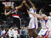 Portland Trail Blazers' C.J. McCollum, left, looks to pass as Los Angeles Clippers' DeAndre Jordan, center, and Clippers' J.J. Redick, right, defends during the second half of an NBA basketball game, Monday, Nov. 30, 2015, in Los Angeles. The Clippers on 102-87.
