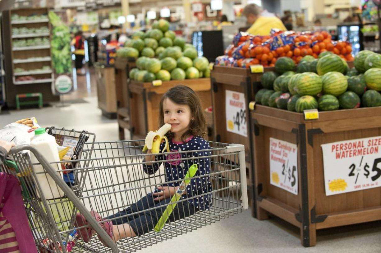 Maisy Fels, 3, of Vancouver snacks on a free banana while shopping with her grandmother Katy Miller on Tuesday afternoon at the Fisher's Landing Fred Meyer. The grocery chain recently launched its Fruit for Kids program that offers children a free piece of fruit while shopping.