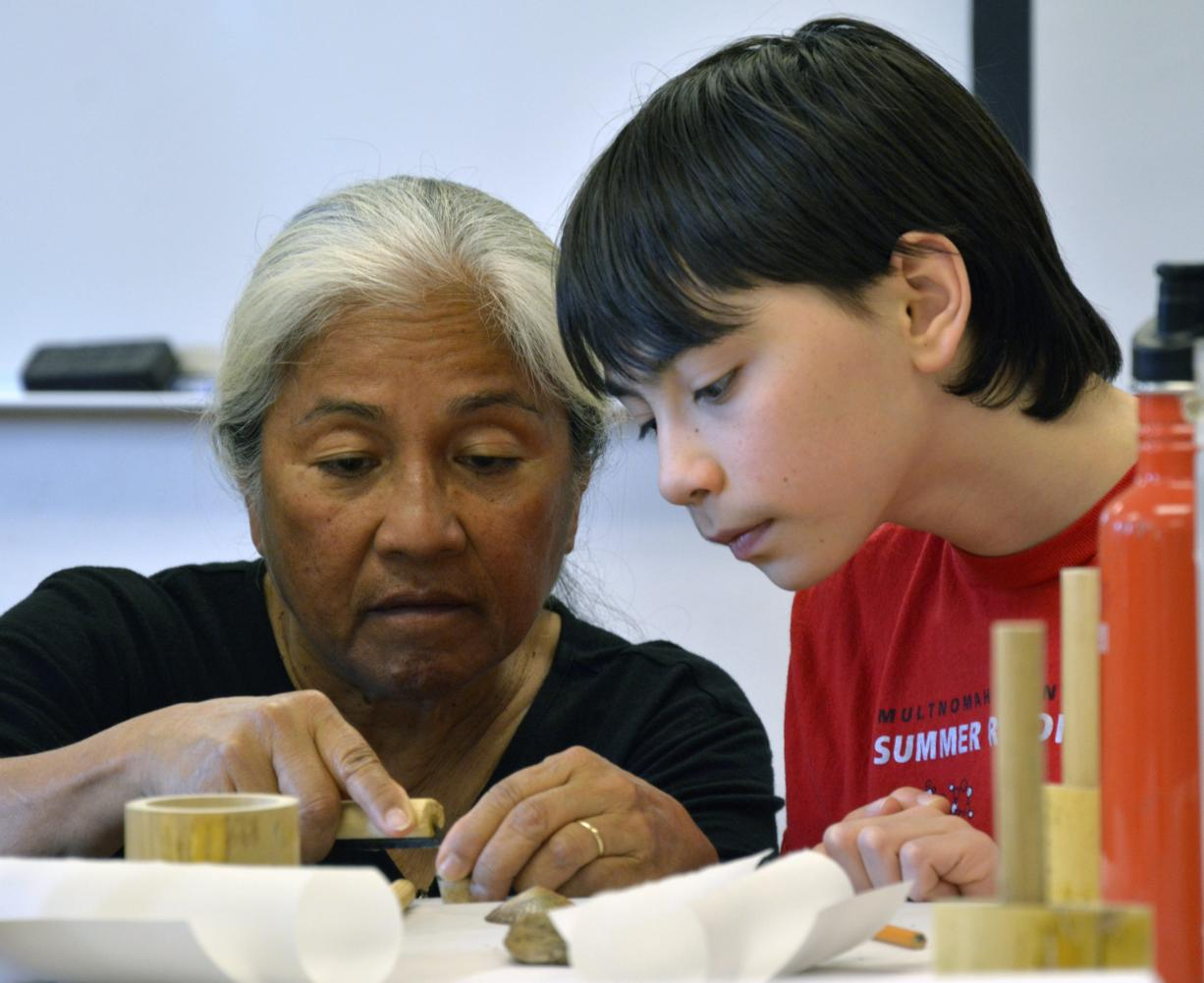 "Bernice Akamine, left, helps 12-year-old Davin Carsten of Vancouver carve a pattern into a piece of bamboo Sunday afternoon during a stamp-making workshop at Clark College. Akamine's art is included in a show titled ""Woven: The Art of Contemporary Native Basketry"" at the college's Archer Gallery."