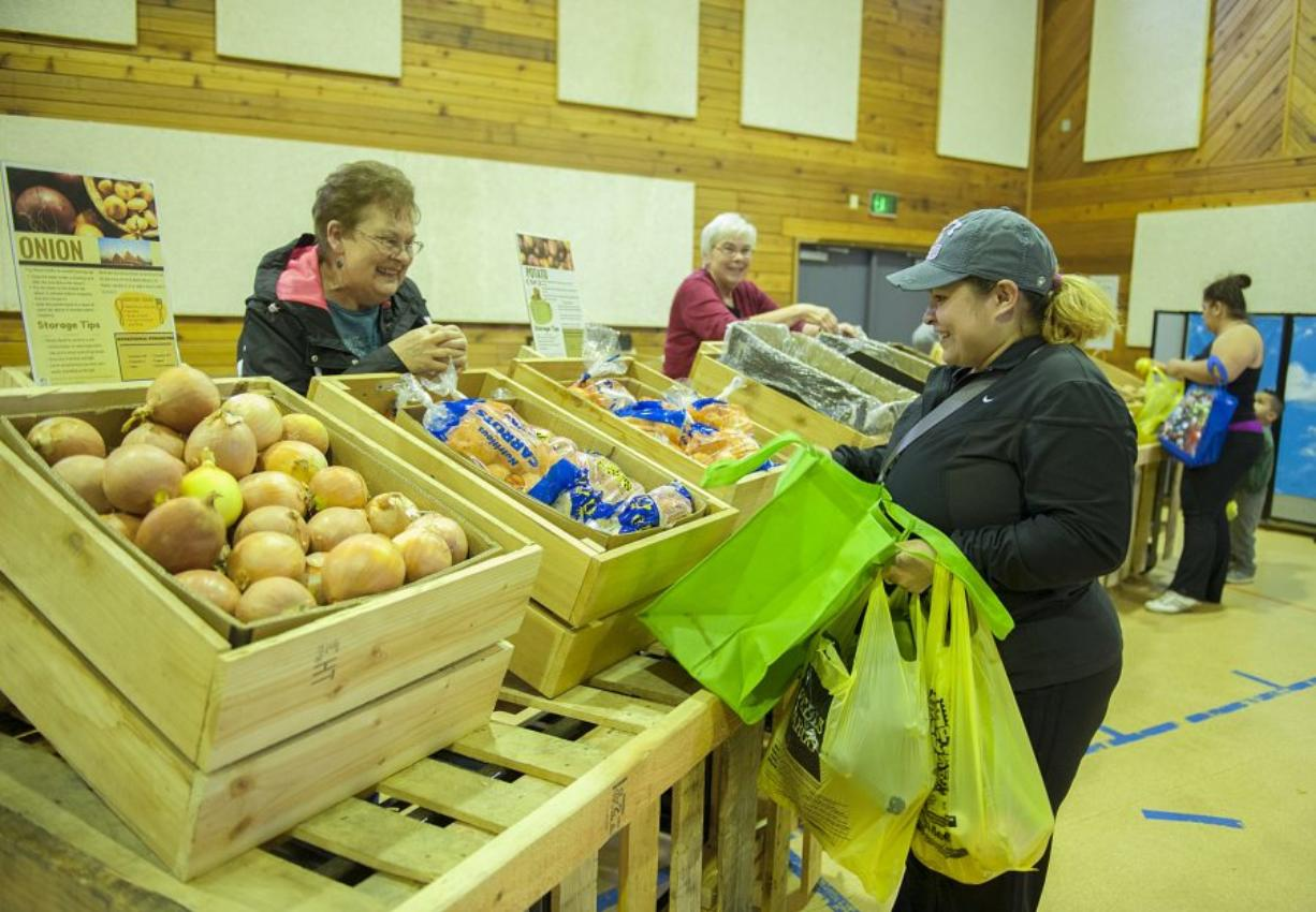 Volunteer Linda Luke, left, assists Martha Aguayo of Vancouver as she shops for produce at a Food Bank Fresh stand set up at St. John Lutheran Church in Hazel Dell.