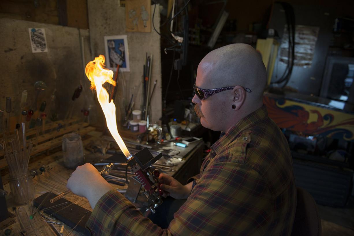Jamie Jenkins of Brush Prairie uses a torch to manipulate glass while making a pipe. Jenkins and other glass artists say their color pallets have shrunk considerably since local manufacturers stopped producing glasses that required heavy metals.