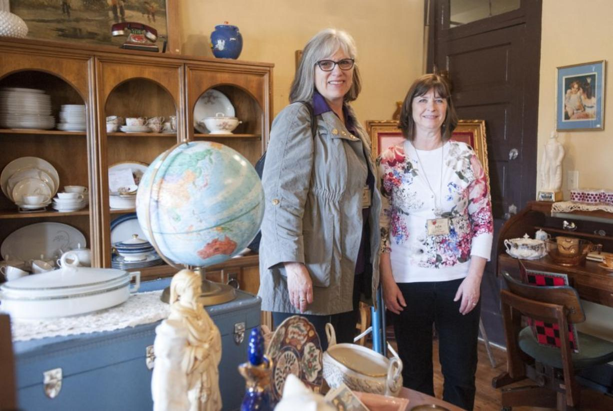 Second Hand Solutions store manager Julie Murray, right, with Judy McMorine, Open House Ministries development director, talk about the new vintage and antique shop opened at the nonprofit's retail building. (Natalie Behring/The Columbian)