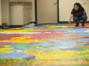 Fort Vancouver High School student Michelle Garcia, a member of the school's MEChA Club, works on a mural Monday that will be hung at the Vancouver Police Department's West Precinct building.
