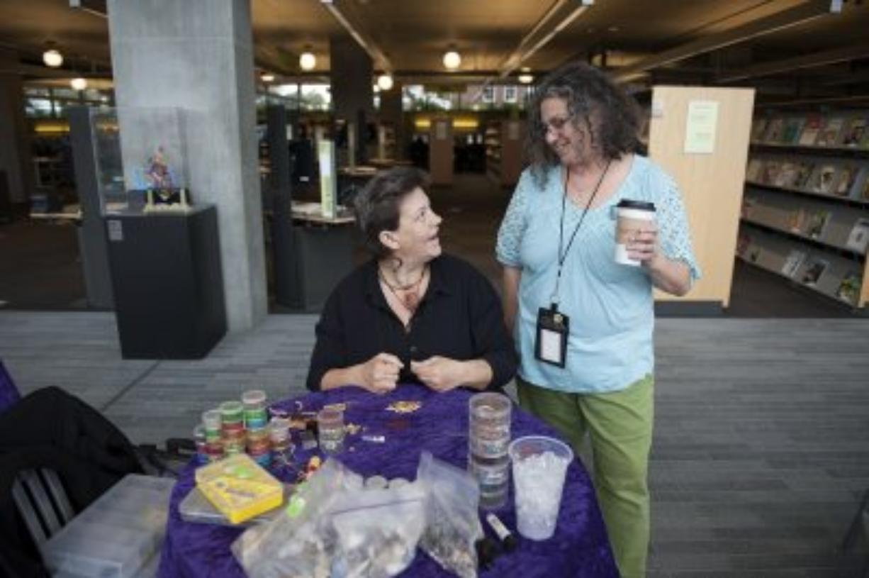 Mandi Vee, left, talks with Vancouver Community Library employee Ruth Shafer while working on a beading project. The two are planning an art gallery featuring artwork done by homeless people.
