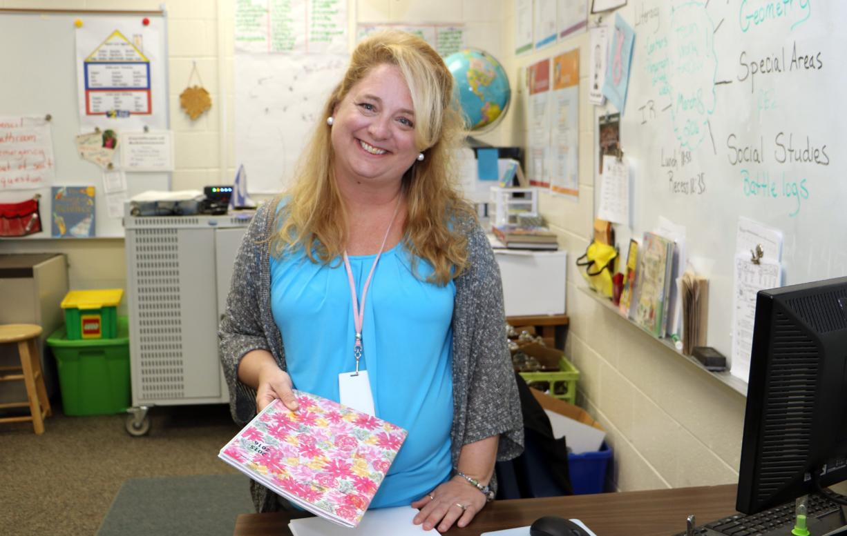 In this March 8 2016 photo, fourth-grade teacher Lori Clarke prepares for her students at Lonnie B. Nelson Elementary in Richland School District 2 in suburban Columbia, S.C. South Carolina's Career Changers loan-forgiveness program nearly covered the cost of Clarke's master's degree in education from the University of South Carolina. After graduating, $45,000 worth of loans were erased over three years of teaching at a high-poverty school in the Columbia area. She now works in a nearby school district. (AP Photo/Seanna M.