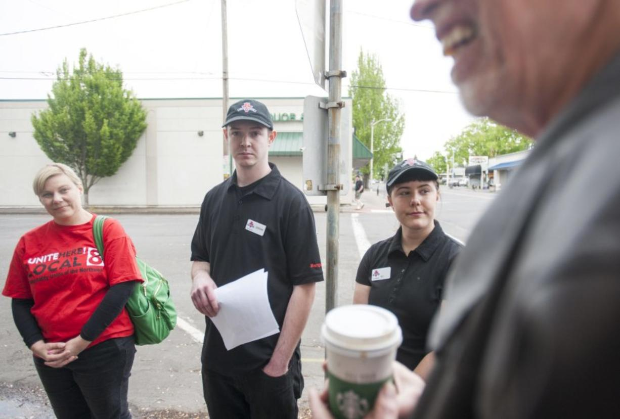 Burgerville employees Jordan Vaandering, second left, and Eli Fishel, second right, Jennifer Graham, left, and the Rev. David Wheeler of Portland's First Baptist Church visited Burgerville headquarters in downtown Vancouver to bring demands to management for $5 an hour raises and improved health care benefits for workers. The visit coincided with a union-backed rally at a Burgerville in Southeast Portland.