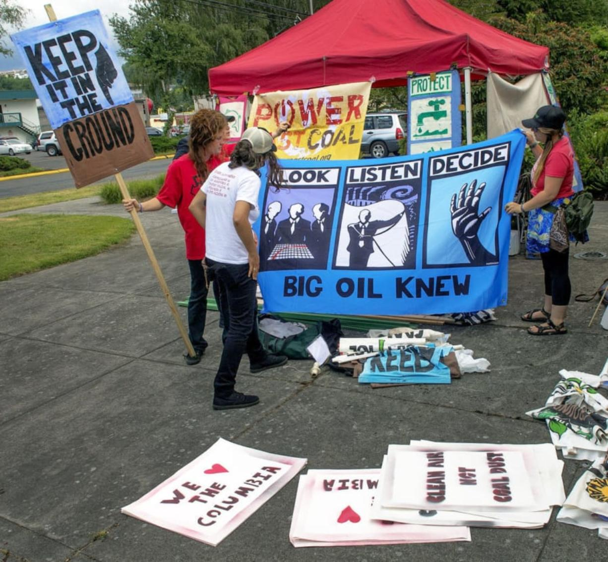 Opponents of the proposed Millennium Bulk Terminals in Longview prepare signs for display at the Cowlitz County Convention Center on Tuesday morning. (Roger Werth/The Daily News)
