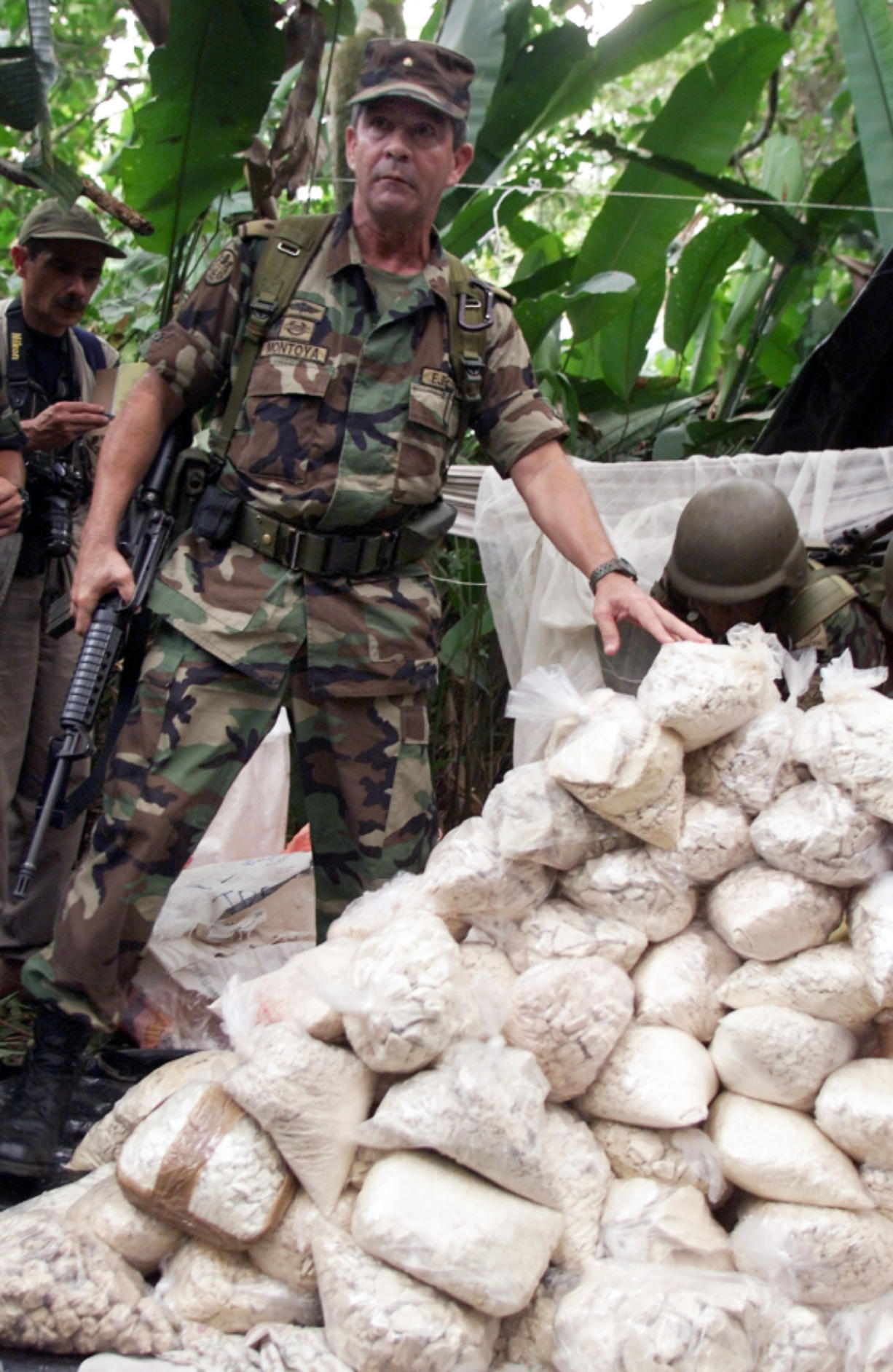 In February 2001, Gen. Mario Montoya of the U.S.-backed military unit in charge of counter-narcotics efforts in Colombia's southern coca-growing region stands next to a pile of coca bags seized at a cocaine laboratory near Puerto Asis, Colombia.