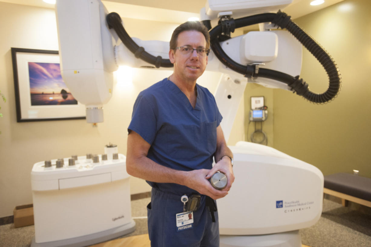 """Dr. Michael Myers, a radiation oncologist at PeaceHealth Southwest Medical Center, holds a tungsten collimator with which the """"cyberknife"""" machine in the background """"paints"""" cancerous areas with radiation. Myers has treated 16 prostate cancer patients with the cyberknife, all of whom went into remission with no recurrences."""