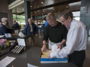 Former Vancouver Mayor Bruce Hagensen, second from right, and City Clerk Lloyd Tyler, right, look through a box of signed petitions Thursday at City Hall. The petition seeks to let voters decide whether the Vancouver City Council's pay hikes should be rescinded.