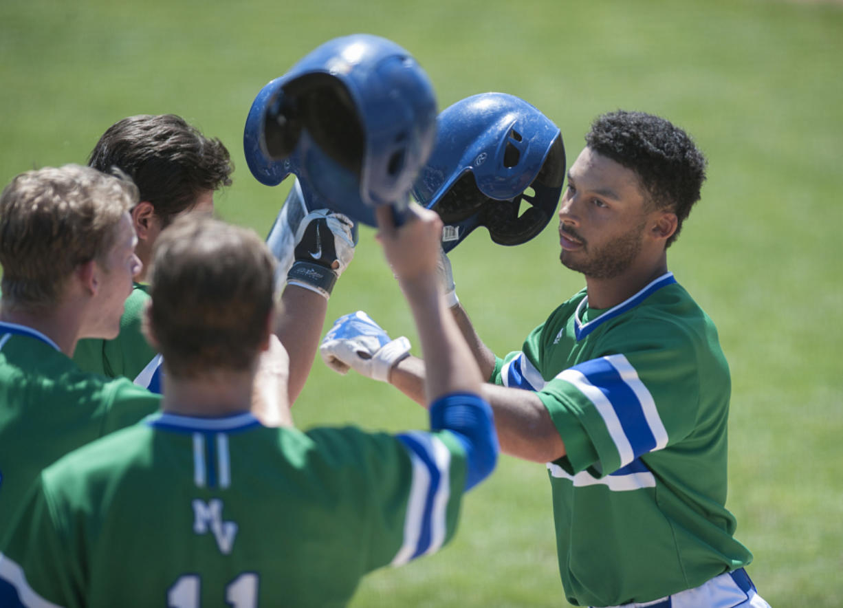 Mountain View's Preston Jones, right, celebrates with teammates after hitting a home run in the first inning Saturday afternoon, May 7, 2016 at Propstra Stadium. (Amanda Cowan/The Columbian)
