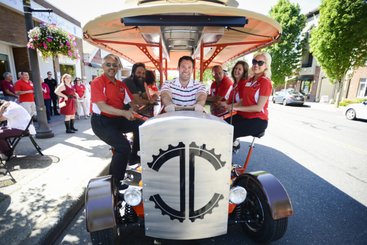 Mayor Tim Leavitt sits in the driver's seat of the Couve Cycle, a pedal-powered party cycle, during the Greater Vancouver Chamber of Commerce's Small Business Crawl in Uptown Village on Wednesday. Owner Michael Palensky sits on the left in the second seat from the front.