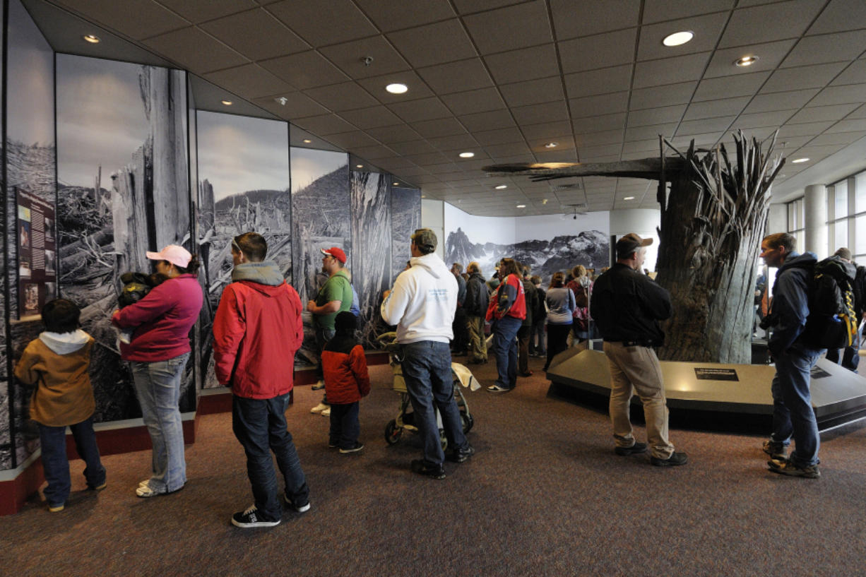 Visitors read about Mount St. Helens near a display of an old-growth tree stump blown over by the volcanic eruption of Mount St. Helens.