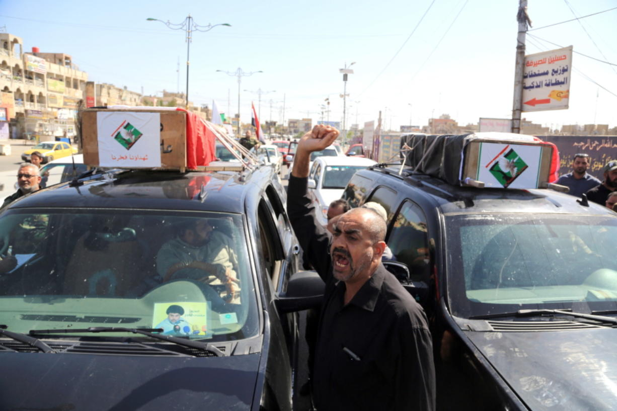 Mourners carry the coffins of two men killed Friday in protests outside Baghdad's Green Zone during their funeral procession Saturday in Baghdad.