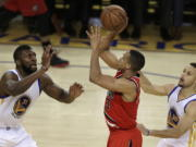 Portland Trail Blazers' C.J. McCollum, center, shoots between Golden State Warriors' Festus Ezeli, left, and Stephen Curry during the second half in Game 5 of a second-round NBA basketball playoff series, Wednesday, May 11, 2016, in Oakland, Calif.