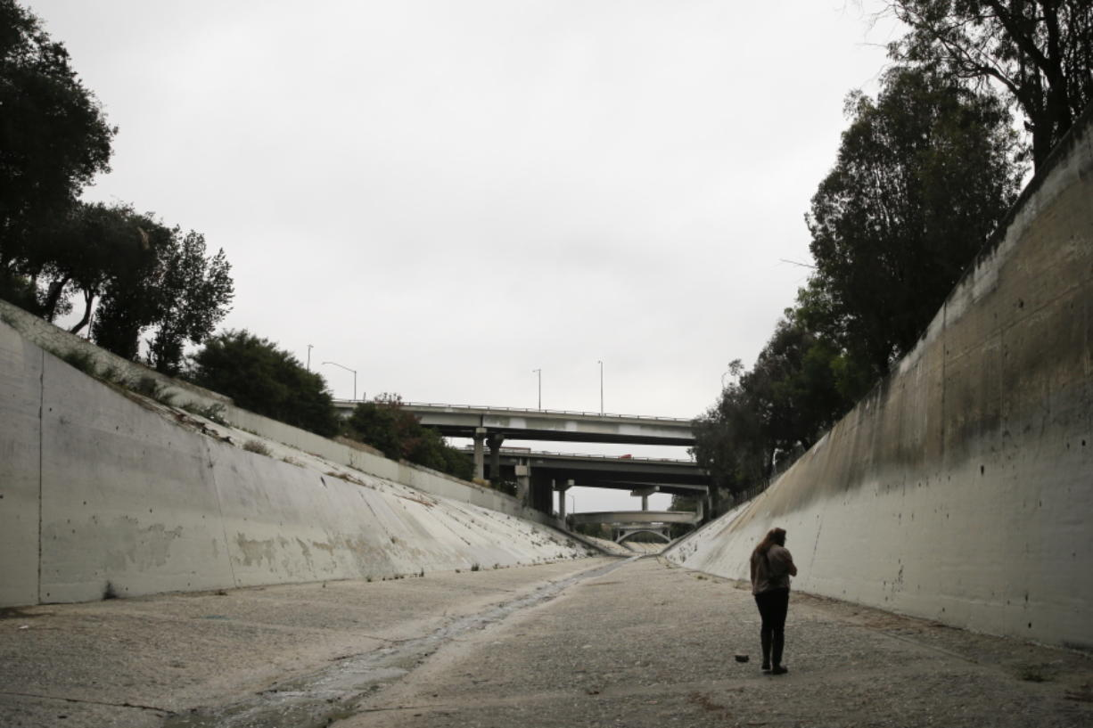 Anthropologist Susan Phillips walks along the Los Angeles River while searching for graffiti by hobos in Los Angeles. Phillips had spent a career examining the graffiti that covers urban walls, bridges and freeway overpasses. But when she came across a heretofore unrecognizable collection made not of spray paint but substances like grease pencil and apparently left there for a century, she was stunned. (AP Photo/Jae C.