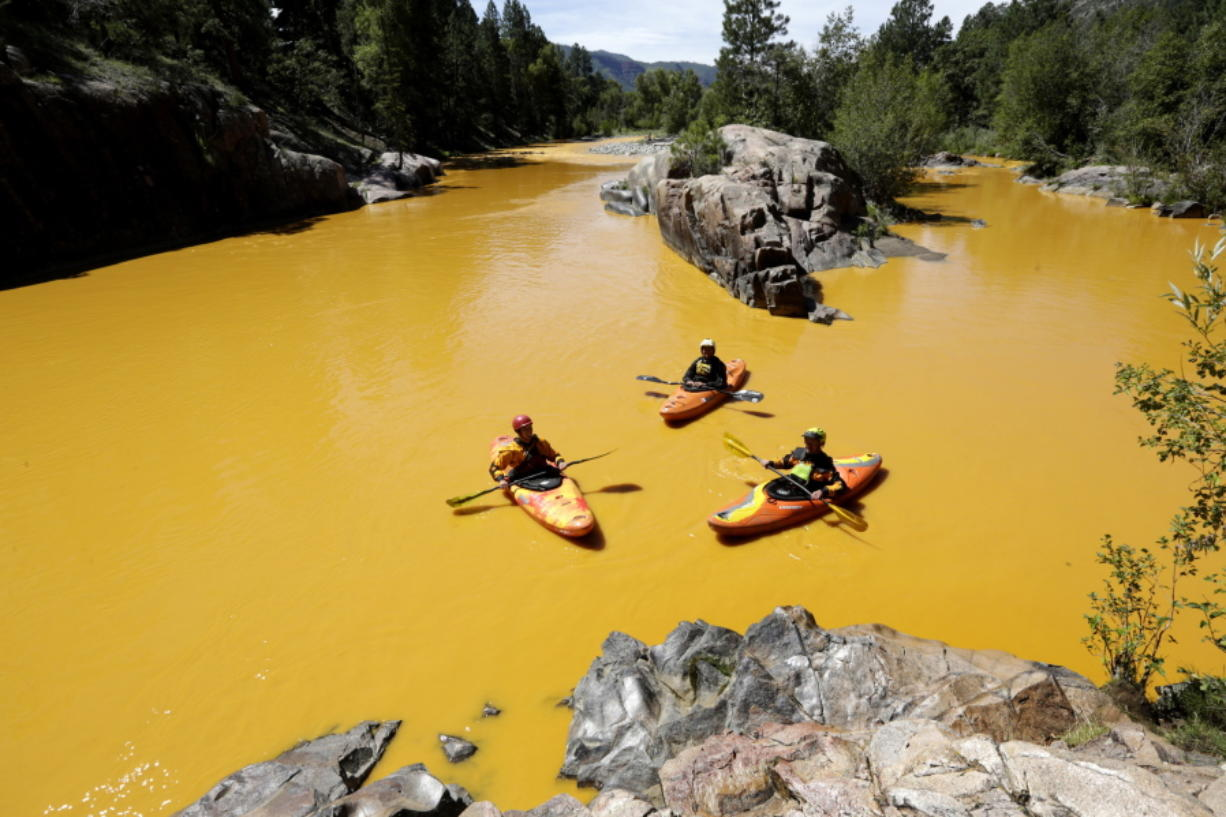 People kayak in the Animas River near Durango, Colo., on Aug. 6, 2015, in water colored from a mine waste spill.