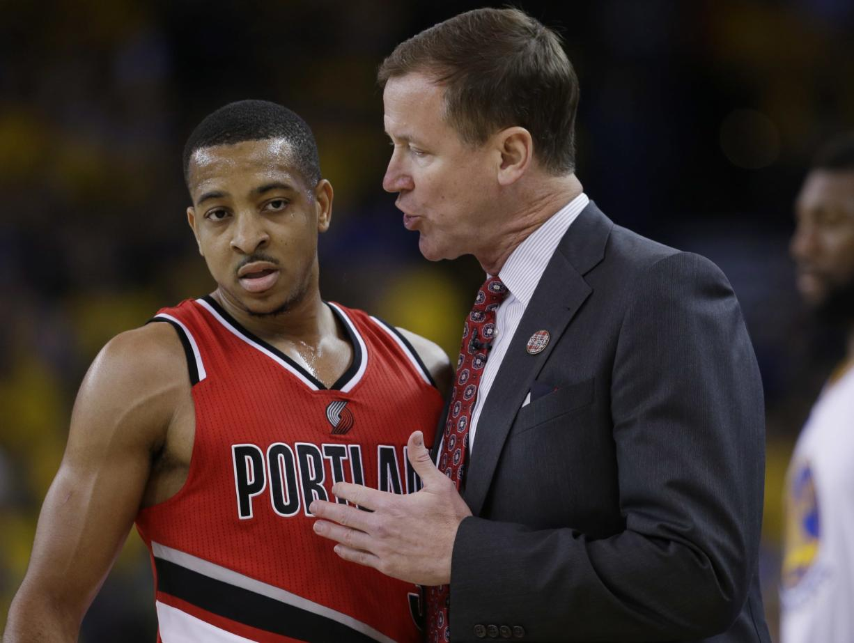 Portland Trail Blazers coach Terry Stotts, right, talks to guard C.J. McCollum during the first half in Game 5 of the team's second-round NBA basketball playoff series against the Golden State Warriors on Wednesday, May 11, 2016, in Oakland, Calif.