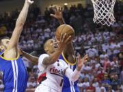 Portland Trail Blazers guard Damian Lillard, right, shoots over Golden State Warriors center Andrew Bogut, left, during the second half of Game 4 of an NBA basketball second-round playoff series Monday, May 9, 2016, in Portland, Ore. The Warriors won 132-125.