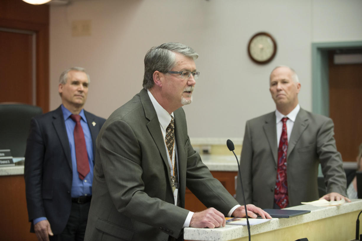County Manager Mark McCauley, center, speaks to the crowd after proclaiming National County Government Month as Clark County Councilors David Madore, left, and Marc Boldt look on at an April Clark County council meeting at the Public Service Center. The council is granted McCauley a new, 18-month contract at Tuesday's meeting.