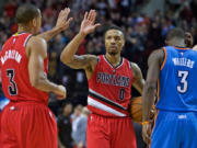 Portland Trail Blazers guard Damian Lillard high-fives guard C.J. McCollum, left, during the second half of an NBA basketball game against the Oklahoma City Thunder in Portland, Ore., Sunday, Jan. 10, 2016. The Trail Blazers won 115-110.