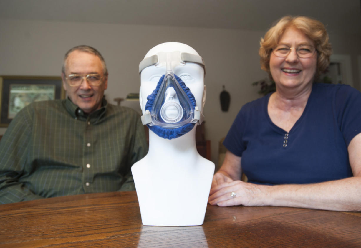 Vicki and Norman Paulk on Wednesday demonstrate the CPAP mask cover they designed at their home in Camas. Norman, who suffers from sleep apnea, invented a soft fabric guard to help make wearing the oxygen mask for an extend period of time more comfortable. (Natalie Behring/The Columbian)
