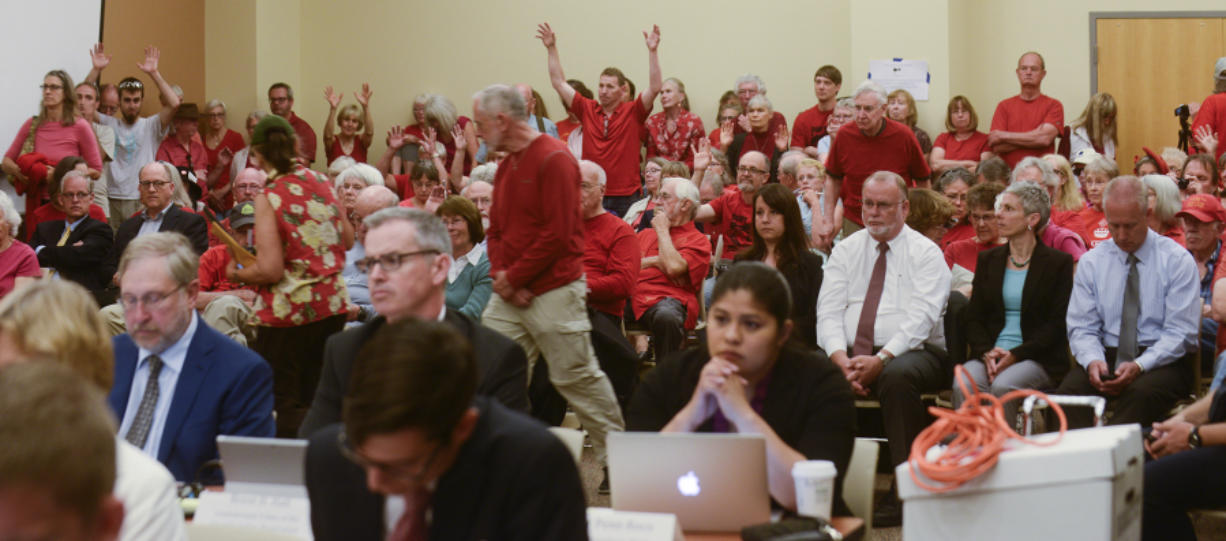 Oil terminal opponents in the audience waive their hands Monday in support of an opening statement critical of the proposed Vancouver Energy oil terminal during an Energy Facility Site Evaluation Council hearing Clark College at Columbia Tech Center.